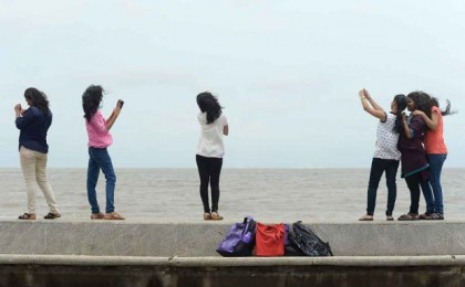 (FILES) In this photograph taken on June 15, 2015, young Indian couples take 'selfies' on Marine Drive promenade in Mumbai.   Mumbai police said January 12, 2016, that they have identified 16 dangerous selfie spots across the Indian city after a man drowned trying to save a girl who fell into the sea while taking a photo of herself. The spots include the major tourist attractions of Girgaum Chowpatty beach and Marine Drive promenade as well as the site where the 18-year-old girl slipped last week, deputy commissioner Dhananjay Kulkarni told AFP.  AFP PHOTO/Indranil MUKHERJEE/FILESINDRANIL MUKHERJEE/AFP/Getty Images